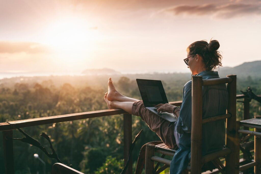 Woman on laptop sitting on deck overlooking a forest and ocean